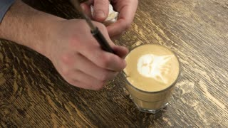 Hand making latte art cat. Frothy coffee in a glass.