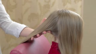 Hand of hairdresser, little girl. Long blonde hair, hairspray.