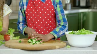 Hand of kid cooking. Chopped lettuce and cucumber.