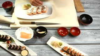 Hand puts caviar onto sushi. Plate with small sushi rolls. Flying fish caviar and rice. Traditional japanese dish with wasabi.
