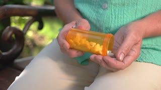 Hand taking white pills. Orange tablet bottle. New strong antibiotic. Protect your health.