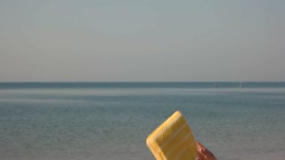 Hand throwing towel, sea background. Flip flop and beach hat. Swim,tan and relax.