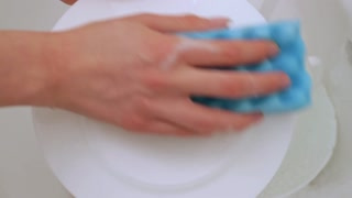 hand wash dishes with sponge