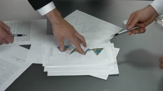 Hands and business charts. Papers on the table. Company must reduce expenses.