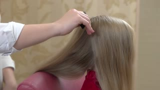 Hands brushing hair in slow-mo. Hairdresser using comb.