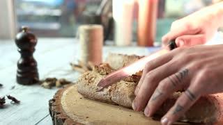 Hands cutting baguette on board. Man breaking bread.