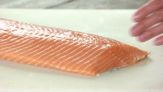 Hands cutting fish. Raw salmon close up.