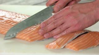 Hands cutting fresh salmon. Sliced raw fish.