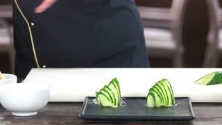Hands cutting salmon. Chef preparing sushi ingredient.