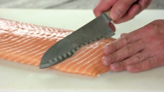 Hands cutting salmon. Raw fish close up.