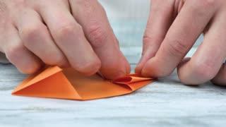 Hands folding origami from orange paper. Japanese paper art workshop. Paper crafting school.