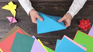 Hands folding paper crane, fast motion. Lesson of origami art. How to make an origami bird.