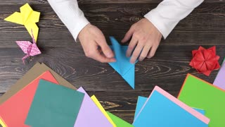 Hands forming blue origami crane. Man doing origami from colorful paper, top view. Different origami figures and colorful paper sheets. Easy handmade gifts.