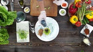 Hands garnishing food top view. Herring tartare, sauce and caviar.