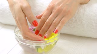 Hands in spa salon receiving treatment. Slow motion female manicured hands in glass bowl with flowers and water. Spa manicure concept.