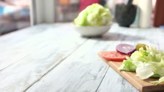 Hands making sandwich with lettuce. Sliced bun on wood board. Veggie burger recipe.