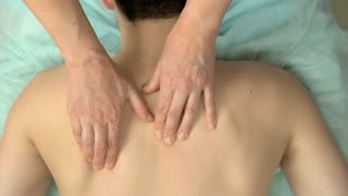 Hands massaging back and neck. Massage top view.