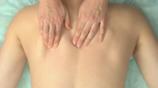 Hands massaging back top view. Person having massage. What is osteopathy.