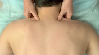 Hands massaging upper back. Top view of massage.