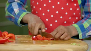 Hands of boy cutting paprika. Kid cooking food.