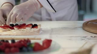 Hands of chef making dessert. Cottage cheese and fresh berries.