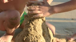 Hands of child, wet sand. Kid playing outdoor. Easy sandcastle designs.
