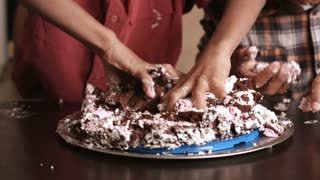 Hands of children destroying cake. Kids smash cake with hands. Neighbour gets his revenge. It's already enough.