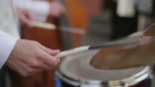 Hands of drummer. The musical group performs. Street musicians. Musicians play. Jazz quartet.