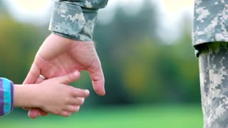 Hands of father and child. Holding hands of military soldier in uniform.