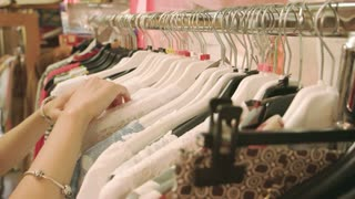 Hands of girl choosing clothes. Clothing on hangers. Sales shopping guide.