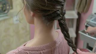 Hands of hairstyist, braid. Female hairdo macro.