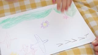 Hands of little girl drawing with colored pencil. Art activity of child. Relax and art therapy.