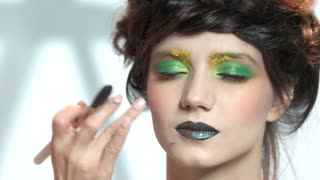Hands of makeup artist working. Face of beautiful female model.