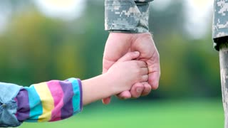 Hands of military father and his daughter. Hands playing of daddy and little girl.