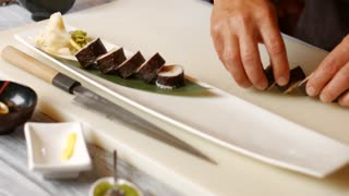 Hands put sushi on plate. Long plate with sushi rolls. Fresh wasabi and special sauce. Japanese chef gives master class.