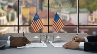 Hands signing papers at table. Handshake of businessmen near flags. Treaty of cooperation. Two american politicians.
