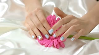 Hands touching gerbera, slow motion. Well-groomed hands with blue gentle manicure and pink gerbera flower on white silk fabric. Female care and tenderness.