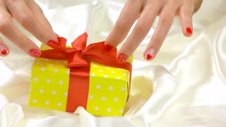 Hands untie gift box, slow motion. Well-groomed hands of young woman unpacking box wirth gift close up. Sensuality and romance.
