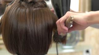 Hands using hair dryer. Female hair and brush.