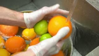 Hands washing citrus fruits. Orange, lime and lemon.