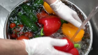 Hands washing fresh vegetables. Bell pepper and tomatoes.