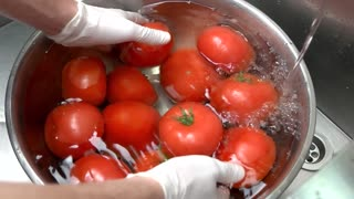 Hands washing tomatoes, slow motion. Red vegetable and water.