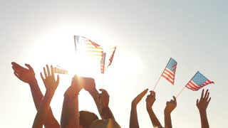 Hands waving US flags. Small flags on sun background. Pride and joy. Happy to live in America.