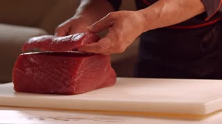 Hands with knife cut meat. Knife cutting meat on board. Chef starts cooking salmon. Even pieces of raw fish.