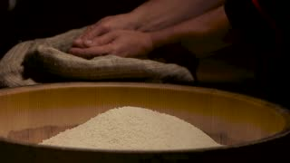 Hands with rice in slow-mo. Groats falling on pile.
