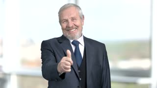 Handsome elderly boss gesturing thumb up. Smiling mature businessman with thumb up gesture on blurred background.