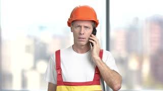 Handsome foreman talking on mobile phone. Mature european builder talking on phone, blurred background.
