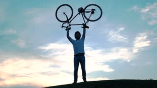 Handsome guy raised bicycle at sunset. Cheerful young man lift a bicycle standing at sunset. Active summer rest and healthy lifstyle. Positive emotions from a trip on bike.