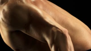 Handsome man building muscles. Close up young athlete having hard training with weight bending forward. Dumbbells exercises tips.