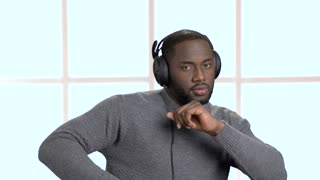 Handsome man in headphones is listening to music. Cheerful afro-american guy listening to music and dancing on checkered window background.
